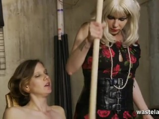 Blonde Mistress Dominates Brunette Submissive With Long Wooden Pole