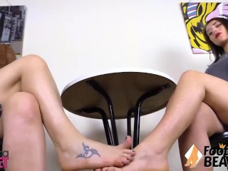 Two girls play footsies under the table